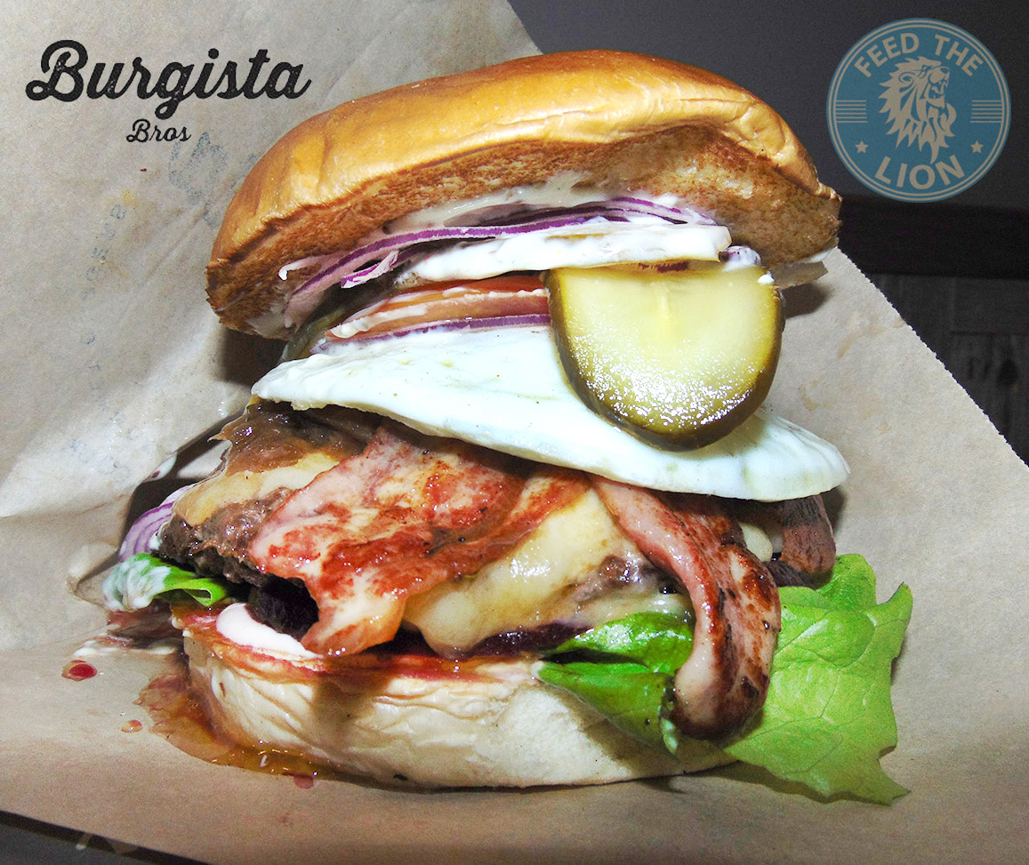 The Australian – Wagyu beef, fried egg, beetroot, turkey bacon, Applewood smoked cheese and onion marmalade, sauce, lettuce, tomato and gherkin in a brioche bun.